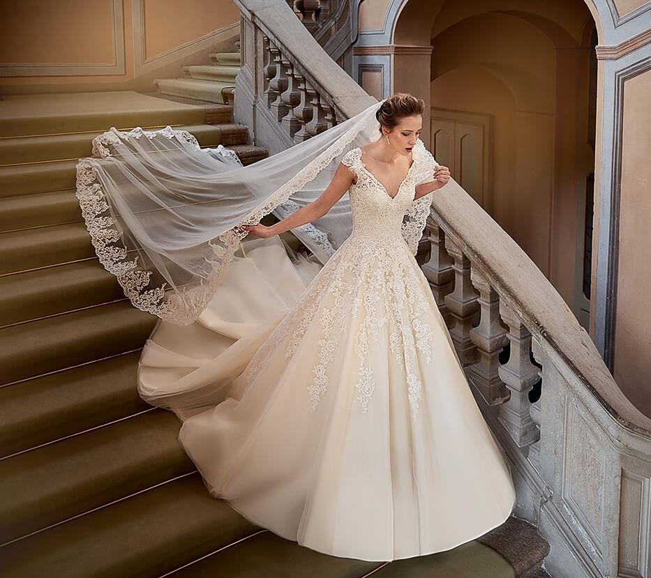 Braut auf einer Treppe mit langem Schleier und Kleid in A-Linie