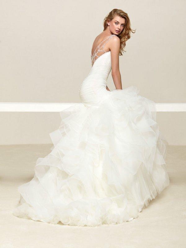 Braut vor beigem Hintergrund mit Meerjungfrauen-Kleid mit Tüllrock