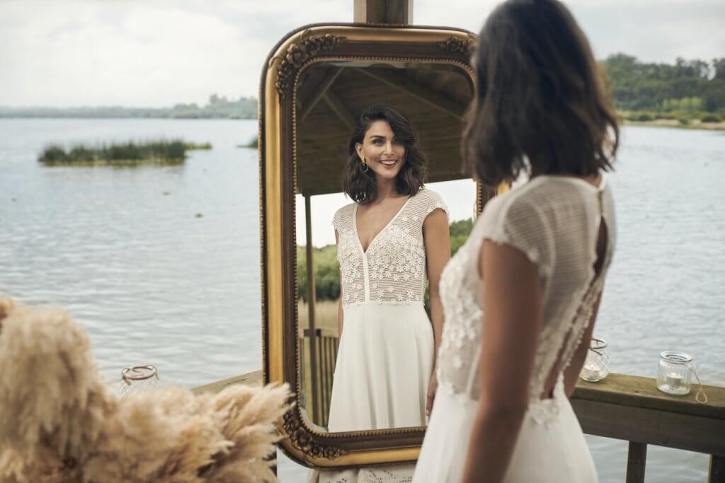 Frau in Brautkleid schaut sich im Spiegel an
