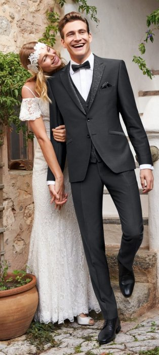 Braut im Boho-Kleid hält die Hand ihres Bräutigams