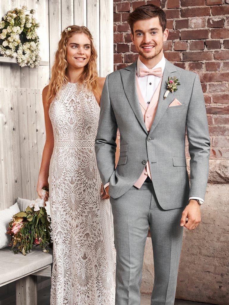 Braut in Boho-Kleid und Bräutigam mit grauem Sacko