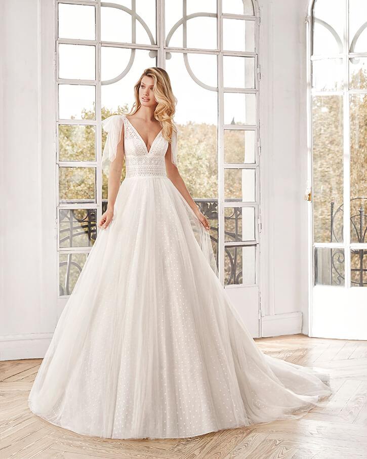 Frau in Brautkleid mit Pünktchen vor Fenster