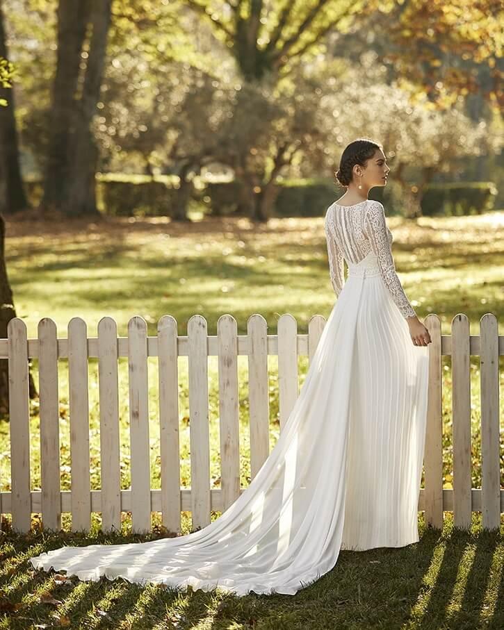 Rückenansicht Braut vor weißem Gartenzaun