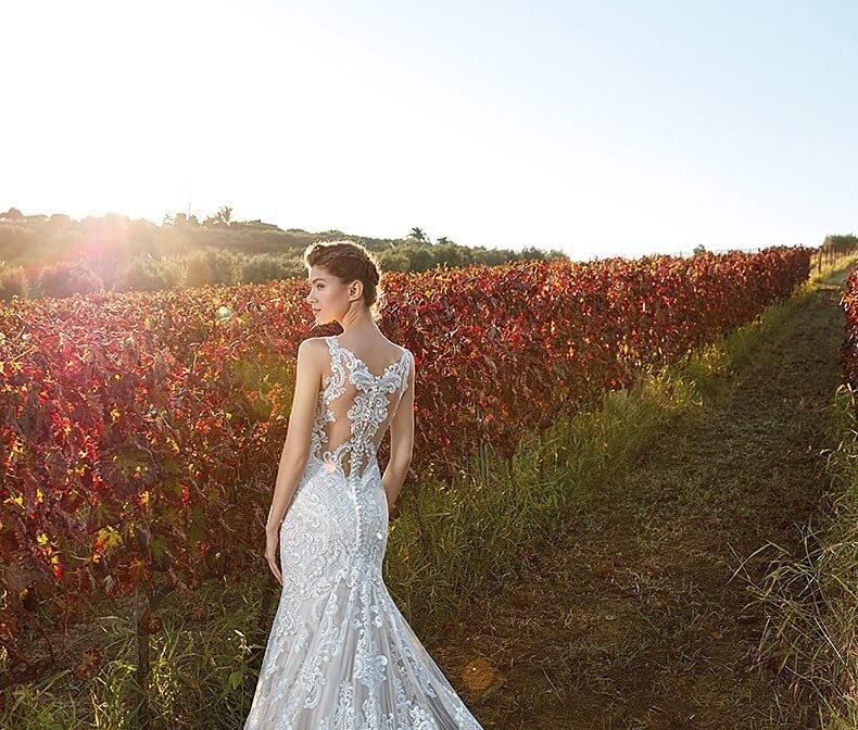 Braut in spitzenbesetztem Brautkleid im Sonnenuntergang