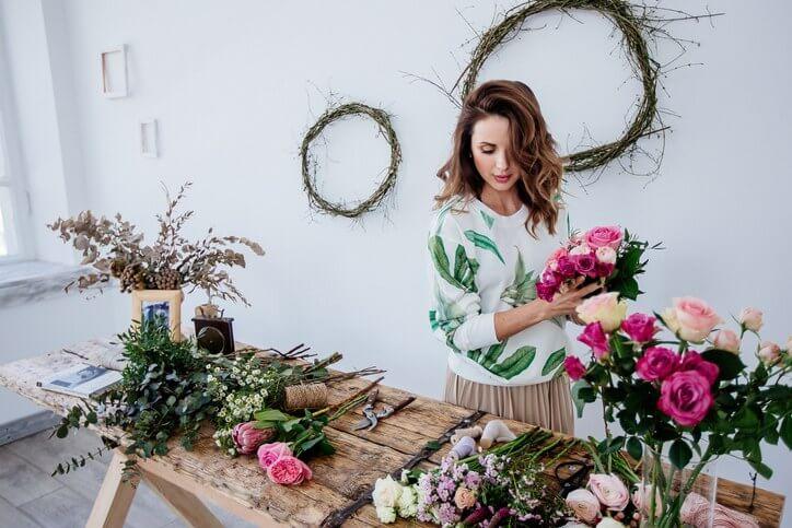 Floristin bindet Brautstrauß in kleinem Atelier