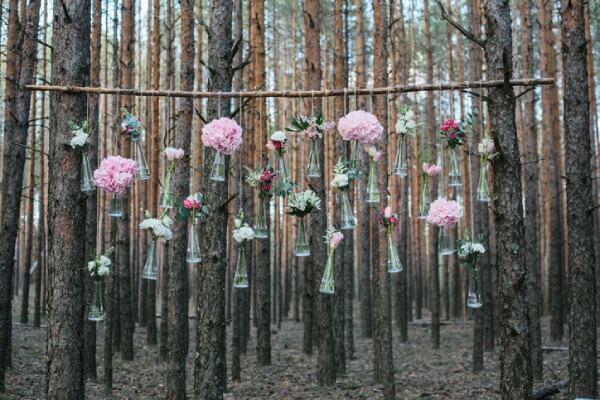 Blumen in kleinen Glasfläschchen an einem Ast hängend