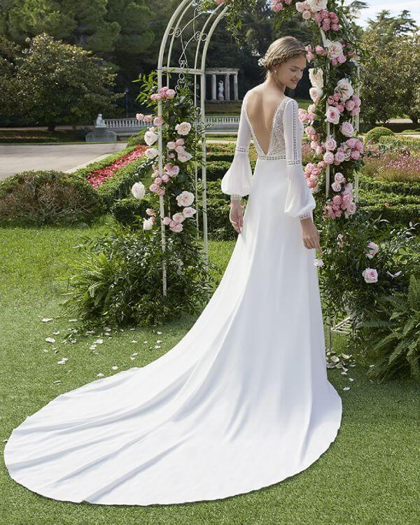Rückenansicht einer Braut unter einem Rosenbogen