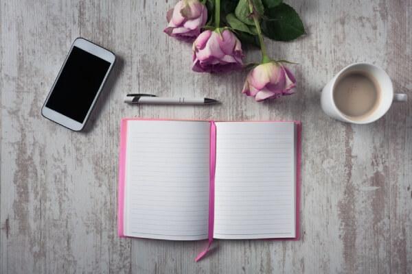 Offenes Notizbuch und Smartphone