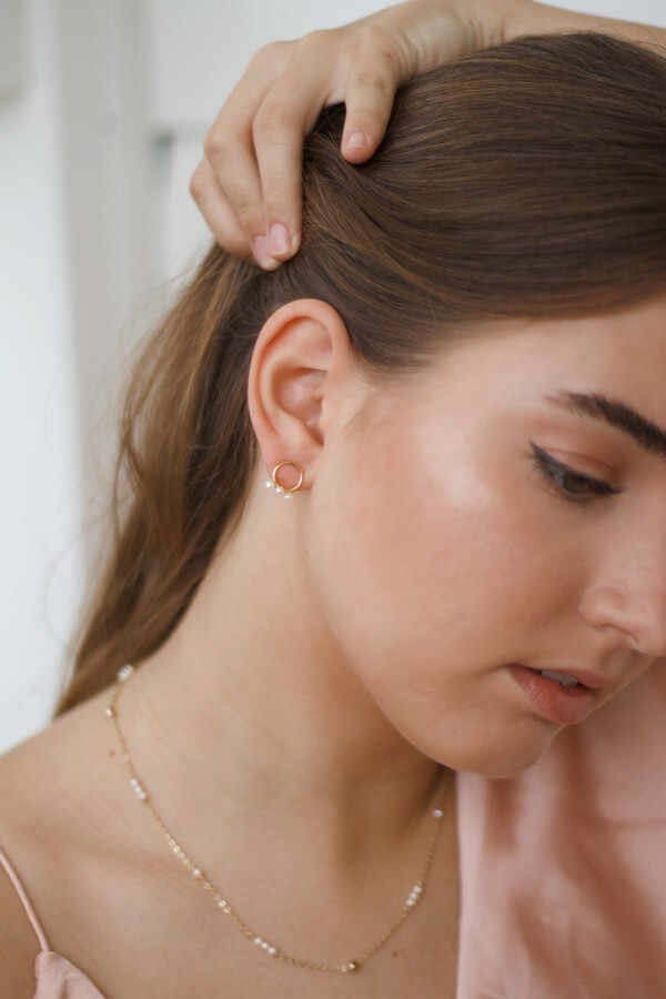 Braut trägt dezenten Ohrringe und Kette